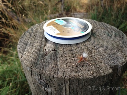 A fishing fly on a stump, with a spool of Maxima Tippet